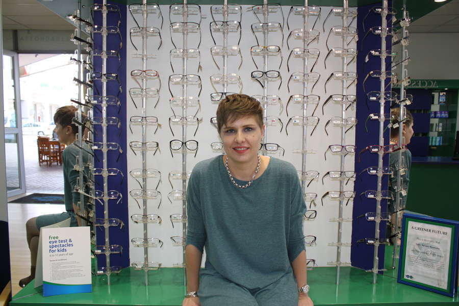 Optometrist Nadia Serfontein in front of some of the frames available at the practice.