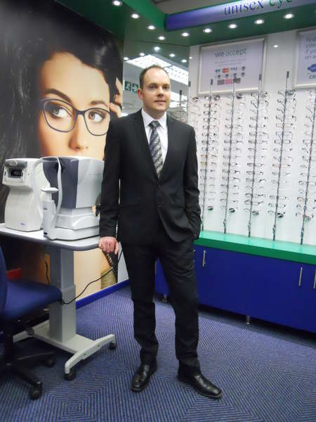 Optometrist (Sean De Kock) standing at the Auto-Refractor & Tonometer.